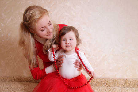 Lovely mother with one year baby girl and red beads photo