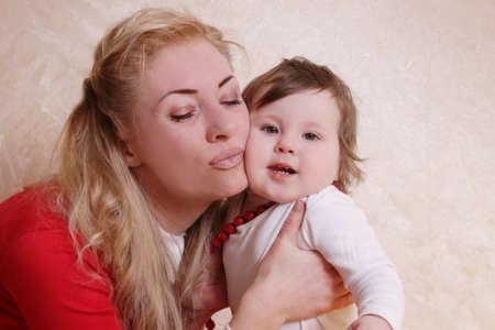 cheek: Mother cheek to cheek with one year baby girl having fun