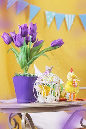 chicken cage: Violet tulips on table with cage and chicken, easter decor Stock Photo