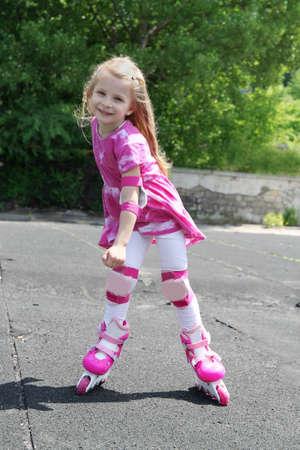rollerskating: Girl in protection rollerskating outdoors