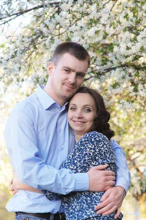 couple lit: Abrazos pareja feliz bajo el �rbol de la puesta del sol de primavera iluminaba