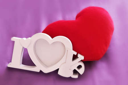 day bed: Plush red heart and word love on magenta back Stock Photo
