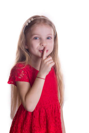 shushing: Blond girl in red dress putting finger up to lips saying shhh isolated on white background