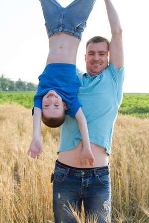 Father holding son upside down in wheat field Stock Photo
