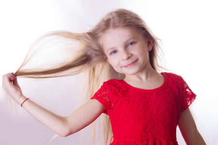unruly: Cute blonde girl in red dress with waving by wind hair