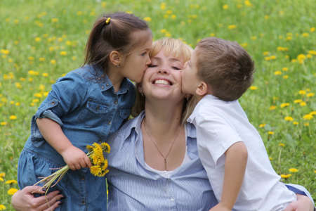 dandelion field: Two kids kissing mother among dandelion field Stock Photo