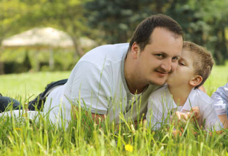 baby facial expressions: Son kissing his father among green grass Stock Photo