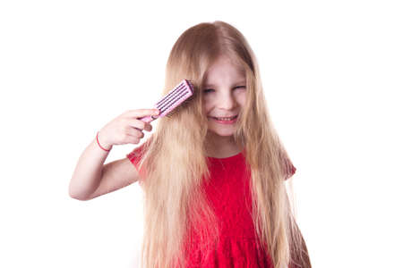unruly: Upset girl combing tangled blonde long hair on white