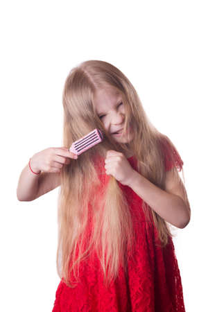 unruly: Upset girl combing tangled long hair on white Stock Photo
