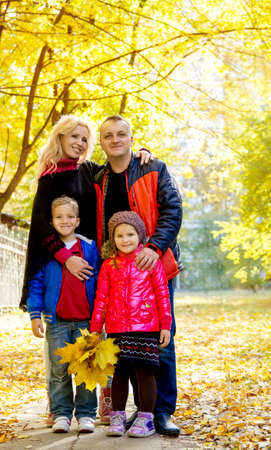 Happy family of four in autumn park