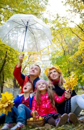 Amazed family of four under umbrella in autumn