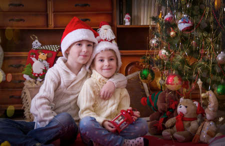 sittting: Sister and brother sittting together under Christmas tree