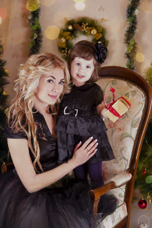 Mother and daughter with gift-box under Christmas tree photo