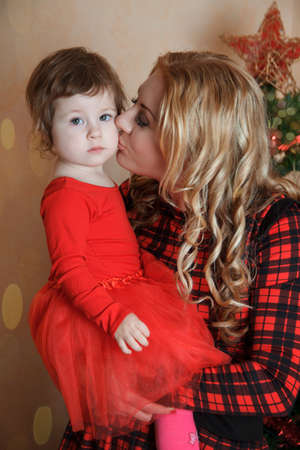 Mother kissing small daughter under Christmas tree photo
