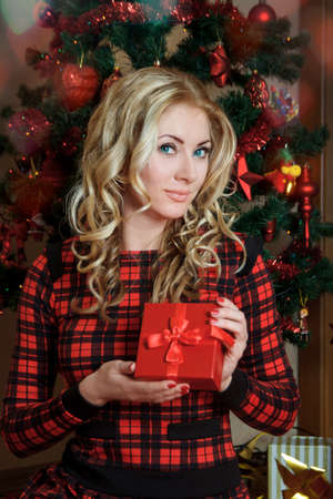 Pretty woman in red dress with gift-box under Christmas tree photo
