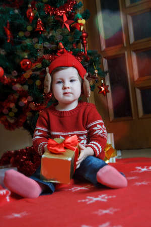 Pretty baby girl with red gift near Christmas tree