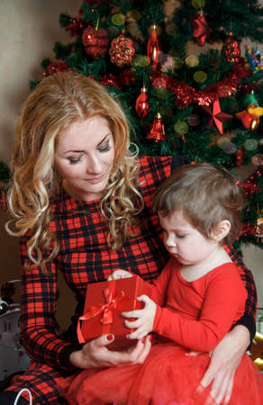 Mother and baby girl under Christmas tree with red gift-box photo