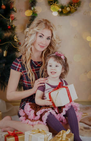 Mother and little daughter with gift-box near Christmas tree photo