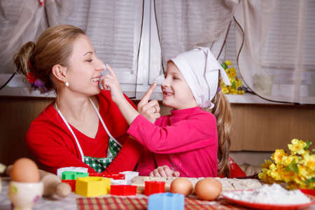 Mother and daughter playing with flour cooking photo