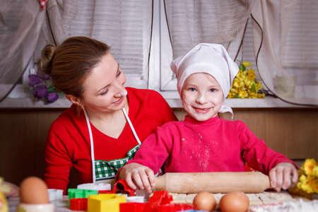 Cute girl rolling dough with her mother photo