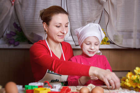 Mother and daughter rolling dough for bisquits photo