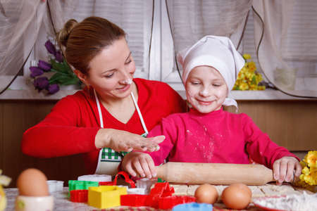 Cute girl rolling dough with her mother for bisquit photo