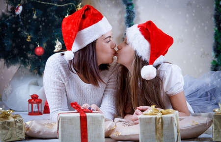 Mother and daughter kissing under Christmas tree Stock Photo - 76257021