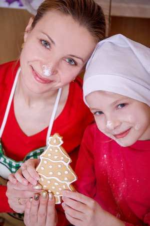Mother and daughter holding Christmas tree biscuit made on kitchen photo