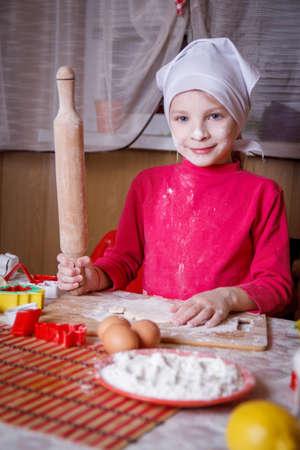 stuff: Girl making dough with rolling pin inkitchen