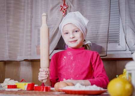 stuff: Girl making dough with rolling pin at kitchen