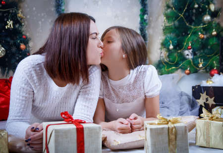 Mother kissing daughter on cheek under Christmas tree