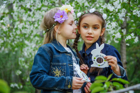 Two girls with toy bunnies telling secrets on ear photo