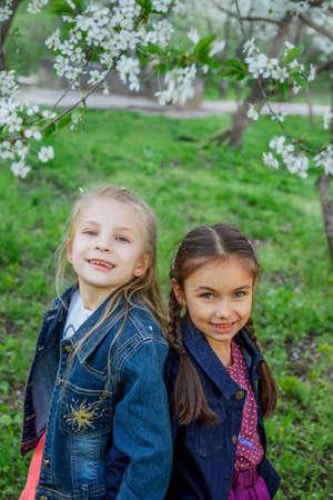 Two happy girls enjoying falling petals in spring garden photo