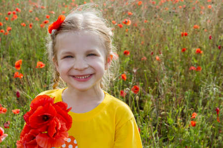 Smiling girl holding bouquet poppies among field photo