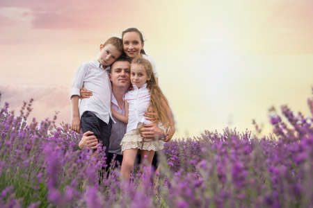Happy family of four in lavender field at sunset photo