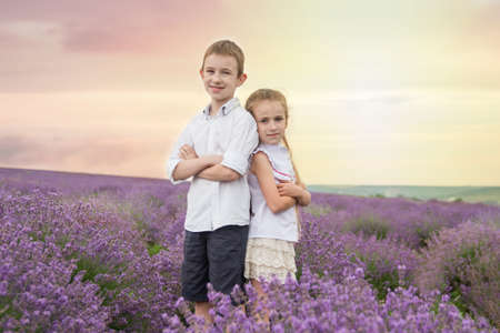 Happy brother and sister in lavender summer field back-to-back photo