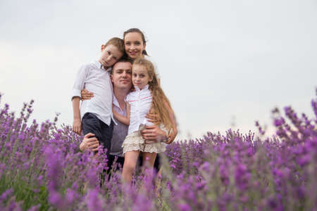 Happy family of four in lavender field over white photo