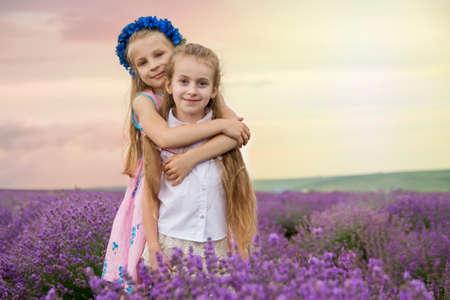 Two cute girls hugging omong lavender field photo