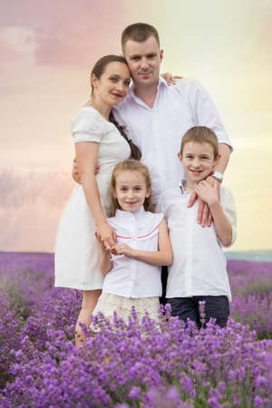 Family of four among lavender field at sunset photo