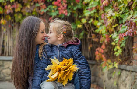 Mother and daughter nose-to-nose among autumn
