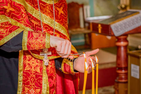 Priest hand burning hair in candle light at orthodox church