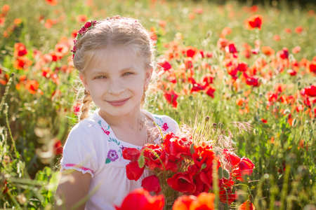 young girl with bouquet among poppies field at sunset