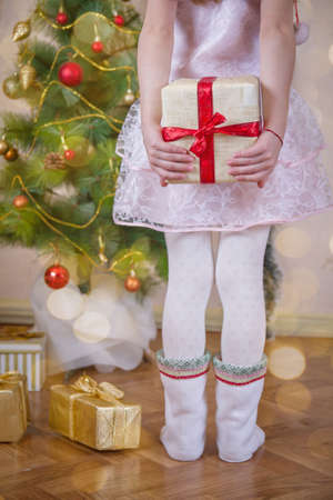 Girl hiding gift after back near Christmas tree, close-up view