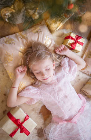 Cute girl dreaming under Christmas tree with gifts, top view Stock Photo