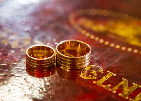 Two wedding rings on bible, on church altar
