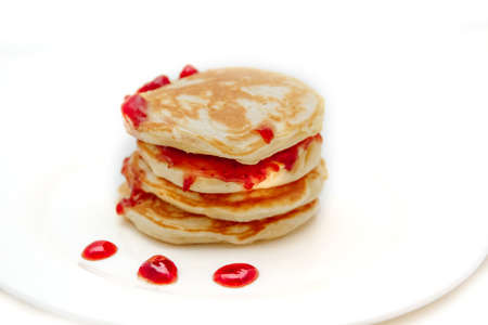 Pancakes with strawberry jam white plate. Selective focus