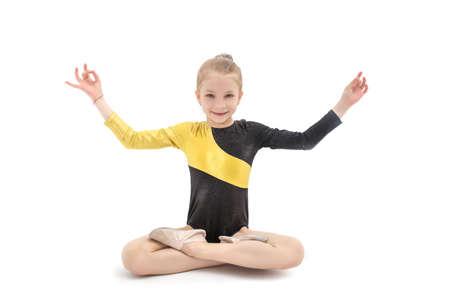 Małe dziecko dziewczynka gimnastyczka siedzi w pozycji jogi na białym tle