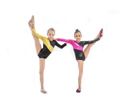 Two gymnastic girls in leotard with leg up isolated on white