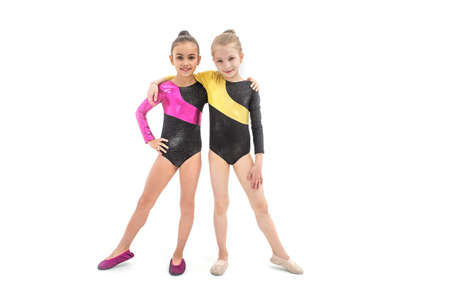 Two gymnastic girls in leotard together isolated on white