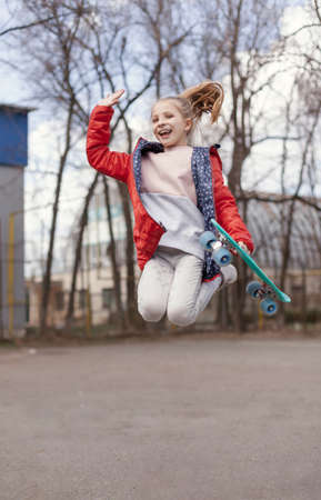 Smiling teen girl with green skateboard in sport park outdoor jumping
